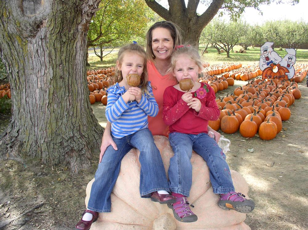 mom with little girls eating carmel apples